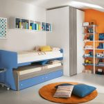 blue trundle beds for children for small bedroom space with double bed and storage underneath plus wall mounted shelving and orange  round rug