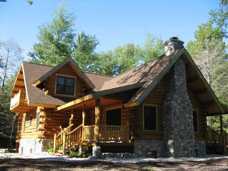 Classic And Rustic Log Cabin Style Home Design With Stone Front Accent Brown Roof