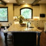 classic kitchen design with large island with seatng and round sinl and giallo rio granite and hardwood floor and white cabinetry