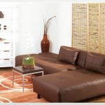 classic room to go sofa design in brown color made of leather on patterned beige area rug with small coffee table and white dresser