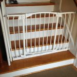 classic staircase design with wooden steps and white colored accent and baby gate for top stairs with door