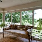 classic white glassed in porch natural wooden furniture wooden floor decorative living plants green backyard view