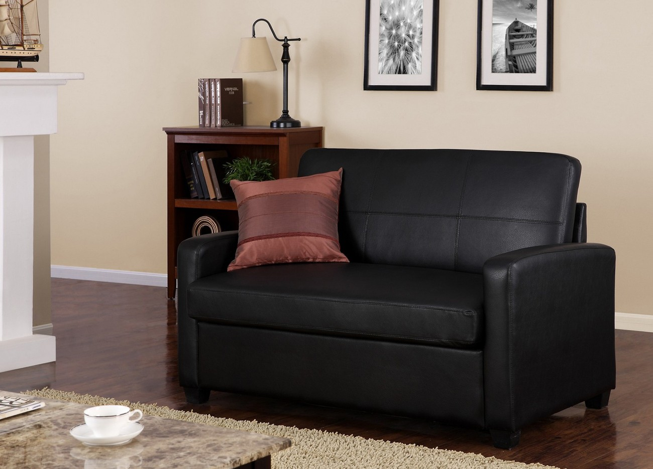 classy black leather single sleeper chair decorated in the living room with decorative cushion and beige rug plus wooden side board