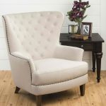 classy white tufted wing chair for oversized accent chair with wooden legs on wooden floor aside wooden side table beneath brick wall