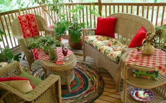 colorful adorable round recycled plastic outdoor rugs backyard open deck wicker outdoor furniture red cushions flowers plants in pots chicken porcelaine accents natural wood floor