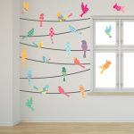 colorful birds on a wire wall art idea on white wall aside glass window with bar frame on wooden floor