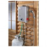 compact grey portable tankless water heater attached on wooden wall