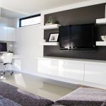 cool flat screen tv wall cabinet with white shelves and media storage and beautified with photo frame and black accent on the wall in modern living room ideas