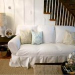 cozy and contended white slipcovered sofa with sophisticated cushions plus wooden coffee table and end table with nice table lamp and brown rug