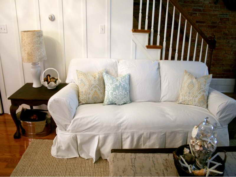 Cozy And Contended White Slipcovered Sofa With Sophisticated Cushions Plus  Wooden Coffee Table And End Table
