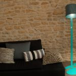 creative turquoise floor lamp decorated in the living room with bucket shade placed aside black sofa with cute decorative cushion and impressive wall from natural stones