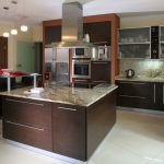 elegant brown kicthen design with wooden cabinetry with giallo rio granite and smokestack and bar