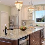 elegant kitchen island idea made of wood with giallo rio granite and wine glass and moroccan pendants aside white cabinetry