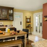 elegant paint color for kitchen in yellow and peach combination with rectangle wooden table with bench and brown wooden cabinetry