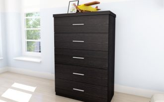 elegant tall black dresser desgn with five drawers and metal handles beneath white wall on beige flooring