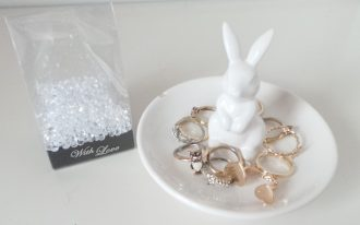 elegant white bunny ring holder design in the shape of rabbit on white plate with rings and box with crystal