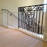 gorgeous and luxurious baby gate for top stairs idea made of scrolled metal in black color with wooden floor and cream painted wall and white stairs
