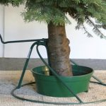 gorgeous firm christmas tree stand for real tree with green bucket and round base green metal on sandy ground