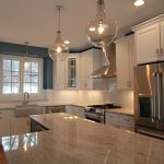 gorgeous large kitchen design with luxurious lighting design and glass window and  river white granite countertop