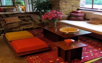 gorgeous open plan living room idea with stone beam and wooden coffee table and red patterned area rug and orange and yellow floor pillow ikea design