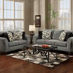 gray couch with patterned loveseat set and rectangle glass coffee table and patterned area rug on hardwood floor with floor to ceiling glass window and potted plant