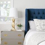 grey wooden campaign side table functioned as nightstand decorated in bedroom with modern table lamp and vase plus rug and blue headboard