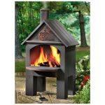 home shaped chiminea fire pit design in black color with chimney and four concrete legs on patio aside lush vegetation