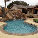 house swimming pool rocks wood waterfall water