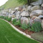 large landscape rocks for natural garden wall green grass and flowers