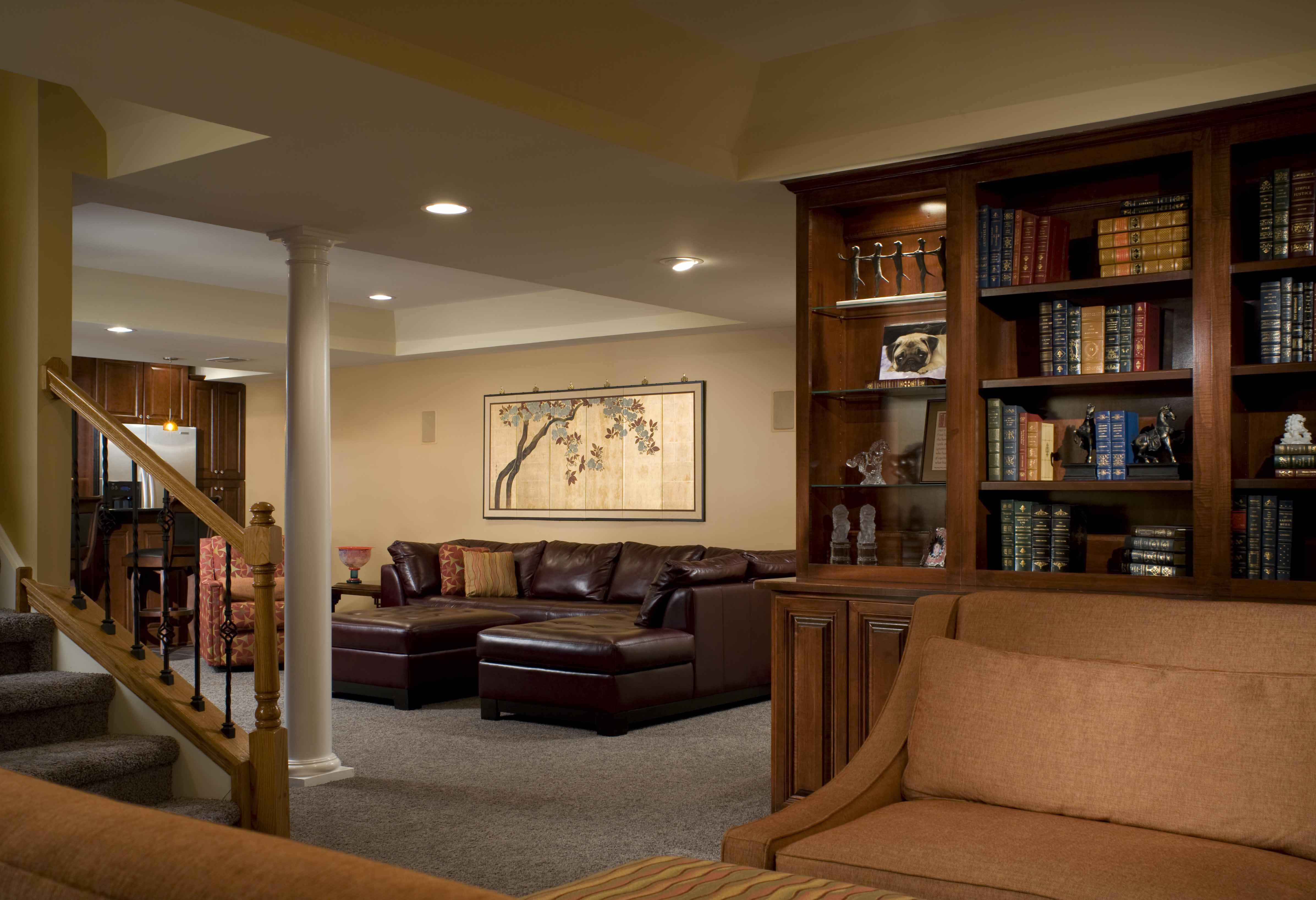 ... Home Makeover Improvement Remodeling. Living Space Basement Remodel  Wood Bookshelf Brown Couches Warm Color Grey Carpet