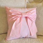 lovely small  light pink pillow design with ribbon accet on furry sofa design