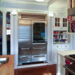 luxurious and large glass door residential refrigerator with double door in kitchen with white cabinetry and white chandelier and hardwood floor