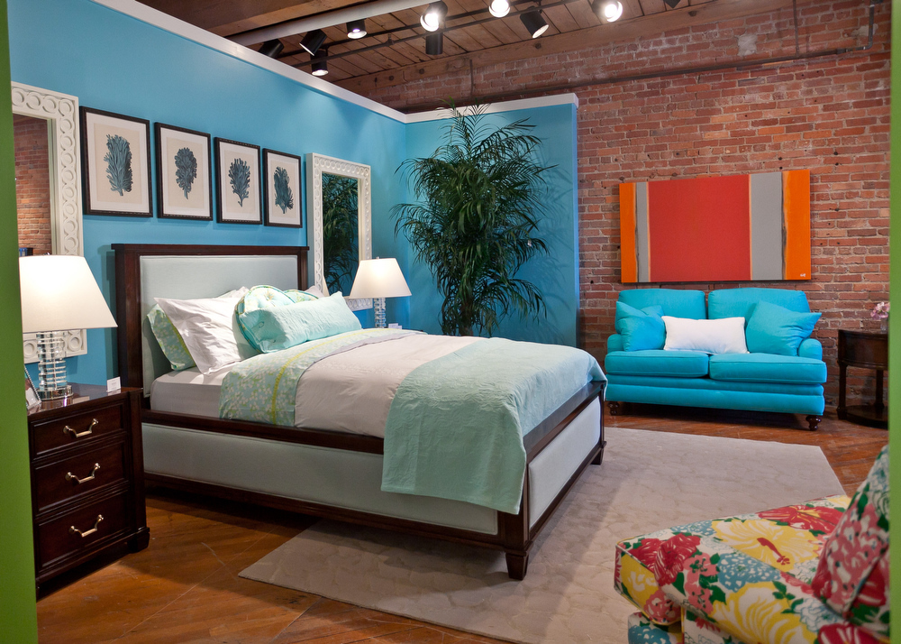 luxurious bedroom design with lilly pulitzer furniture with blue siding and brick wall and orange palette and blue chair and white bedding and gray rug