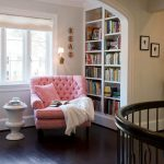 Luxurious Classic Room Design With Recessed Wall Bookshelves And Pink Tufted Cpzy Reading Chair Beneath Glass Wall With Small Round Table On Wooden Floor