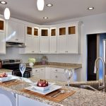 luxurious white kitchen design with white wooden cabinetry and white patterned giallo rio granite idea with sink and curved faucet