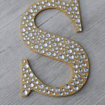 luxurious S shaped large decorative letter design in yellow tone with crystal pouring accent on wooden wall