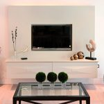 mesmerizing and space saving flat screen tv wall cabinet made of wood decorated with artistic object and beautiful vase and glass coffee table on white painted wall