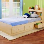 mesmerizing wooden trundle beds for children with three storage underneath and headboard with shelving and rug underneath plus blue curtain and hardwood flooring