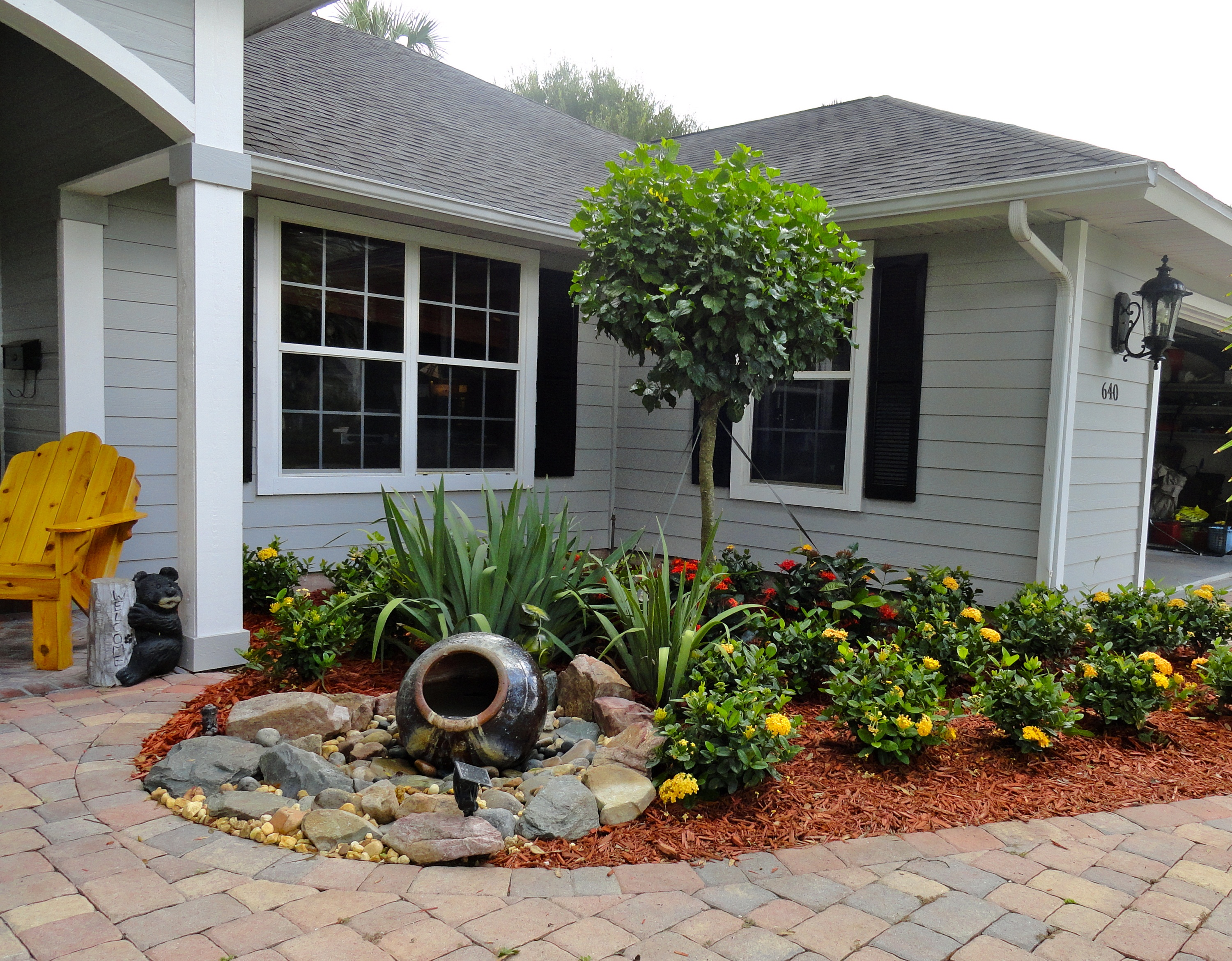 Front yard flower garden ideas - Minimalist Garden With Low Growing Flower And Tree And Natural Stone With Front Yard Fountain Aside