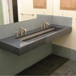 minimalist one sink two faucet design in bathroom vanity with frameless wall mirror and black tile flooring style