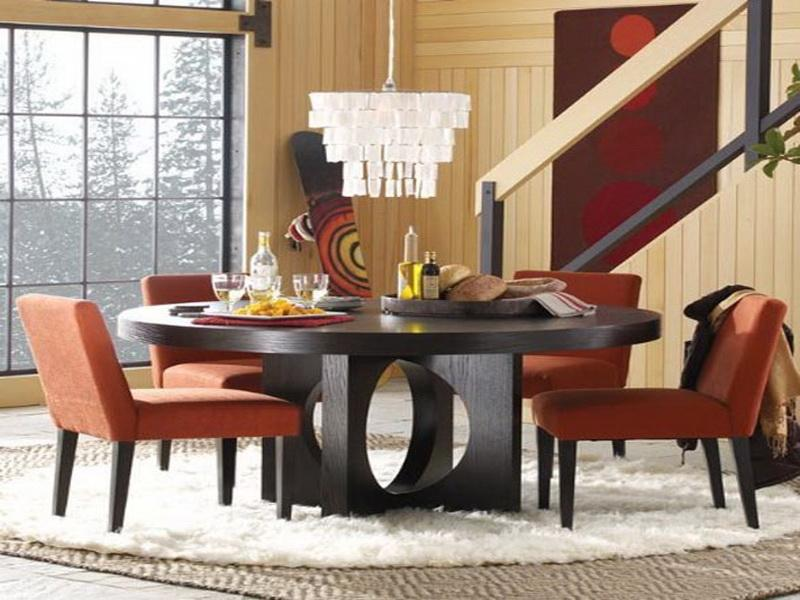 modern and luxurious dining space with chandelier and wooden round kitchen table set with red chairs
