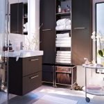 modern bathroom design with brown ikea bath cabinet with white top and large closet and round white table with orchid