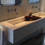 modern bathroom design with long white concrete one sink desgn with two faucets with wooden board and wall mirror and towel hanger