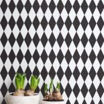 modern black and white diamond shape patterned peel and stick removable wallpaper idea with white table and potted plants