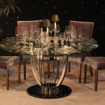 modern design stainless steel table base for glass top big round glass table soft wooden chairs clear glasses on the table nice candles accents