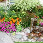 modern front yard garden idea with concrete patio and lower growing flowers and shrub and minimal fountain