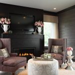 modern living room design with black fireplace and pouf coffee table and brown wing chairs and pink rose decoration and glass window and and metallic grasscloth wallpaper