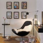modern shaped cozy reading chair in black color with faux fur throw with robot floor lamp on wooden floor with round cream area rug with modern table and picture frame target