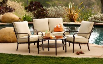 modern target patio chairs in beige scheme with round coffee table and beautiful pool and garden