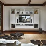 modern white flat screen tv wall cabinet in wood with many shelves for media storage and artworks and tv screen in the center of the cabinet with speaker